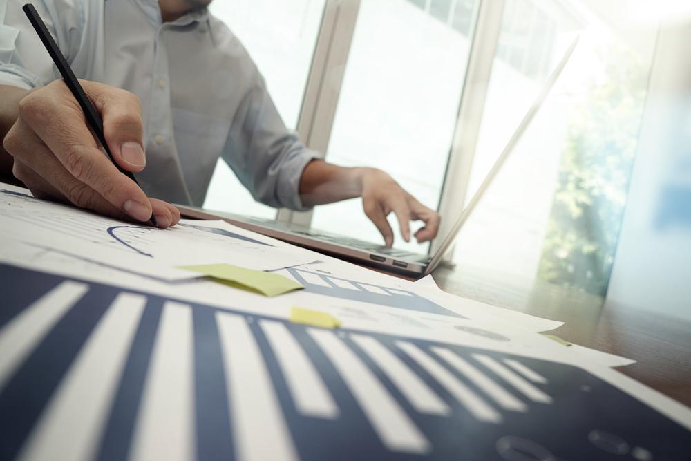Persona trabajando frente a una notebook, con hojas y lápiz.
